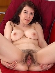 Emily Winters Loves Her Red Sofa, And Shows Off Her Hairy Pussy Up Her Denim Skirt. She Strips Naked And Lays Back To Enjoy Her Body. She Touches Her